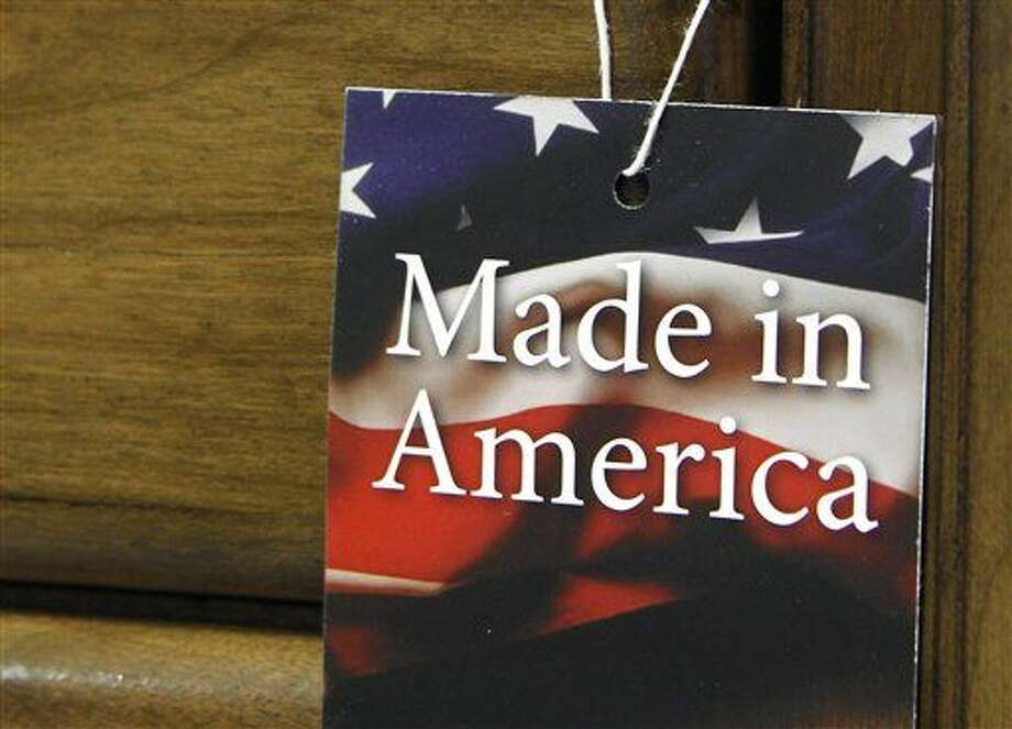 "In this March 16, 2012 file photo, a ""Made in America"" tag hangs on a chest of drawers at a furniture factory in Lincolnton, N.C. The vast majority of Americans say they prefer lower prices instead of paying a premium for items labeled ""Made in the U.S.A.,"" even if it means those cheaper items are made abroad, according to an Associated Press-GfK poll. (AP Photo/Bob Leverone, File) Photo: Bob Leverone"