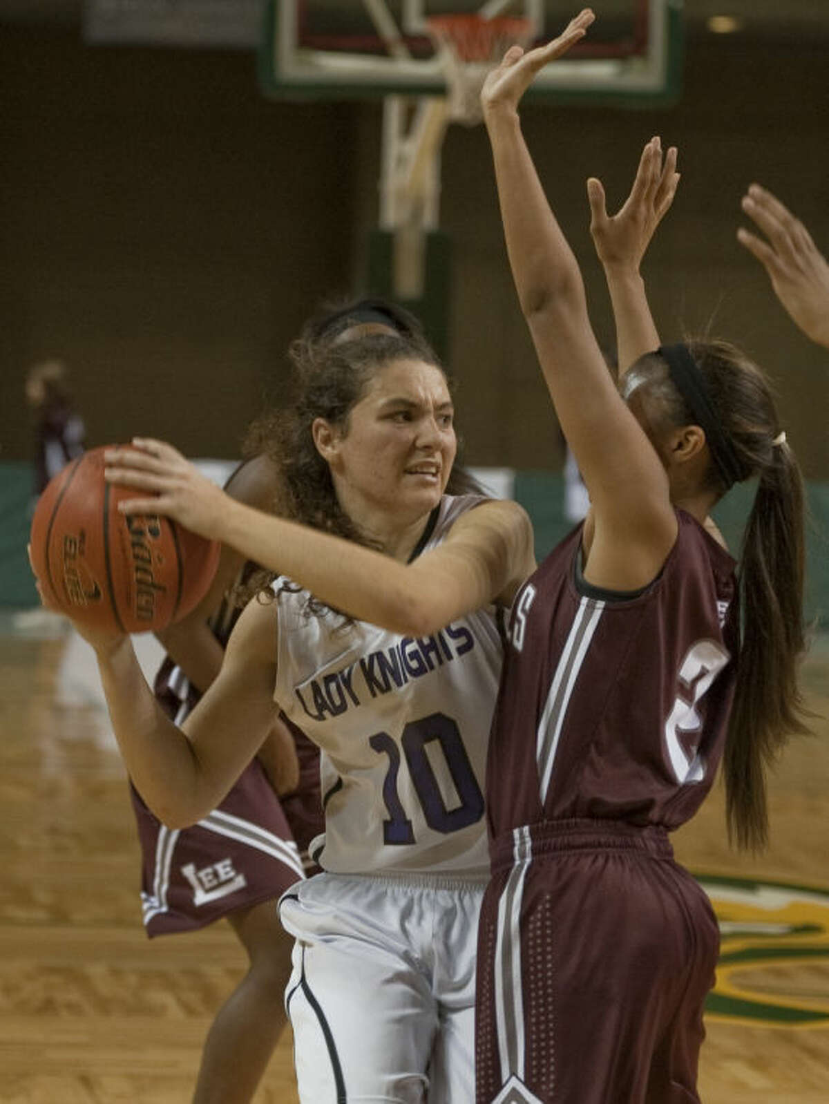 Midland Classical's Kayla Beattie looks to pass inside as Lee's Allison Valdez defends Thursday afternoon in the opening game of the Byron Johnston Holiday Classic basketball tournament. Tim Fischer\Reporter-Telegram
