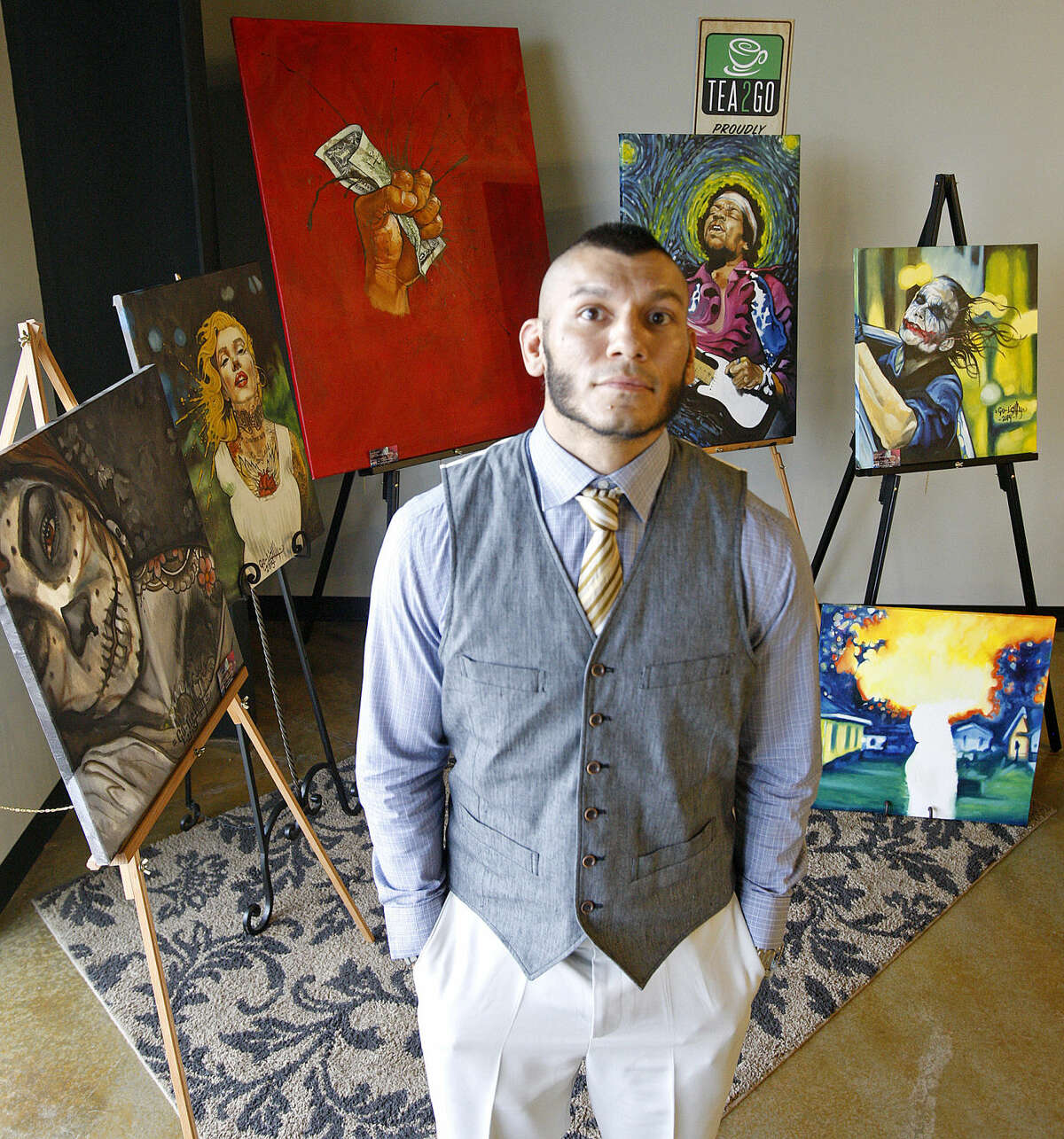 Local artist David Go-Lightly Lopez will display and sell his work at Tea2Go on Saturday as a fundraiser for Zadee Lopez, a 2-year-old with stage 4 cancer. Go-Lightly Lopez is pictured with some of his pieces in portrait Wednesday, April 22, 2015 at Tea 2 Go. James Durbin/Reporter-Telegram