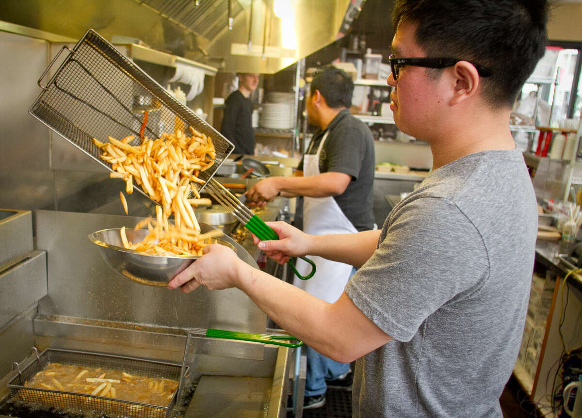 Owner John Chow gets French Fries from the deep fryer at the Little Griddle restaurant in San Francisco, Calif., on Thursday, January 20th, 2012.