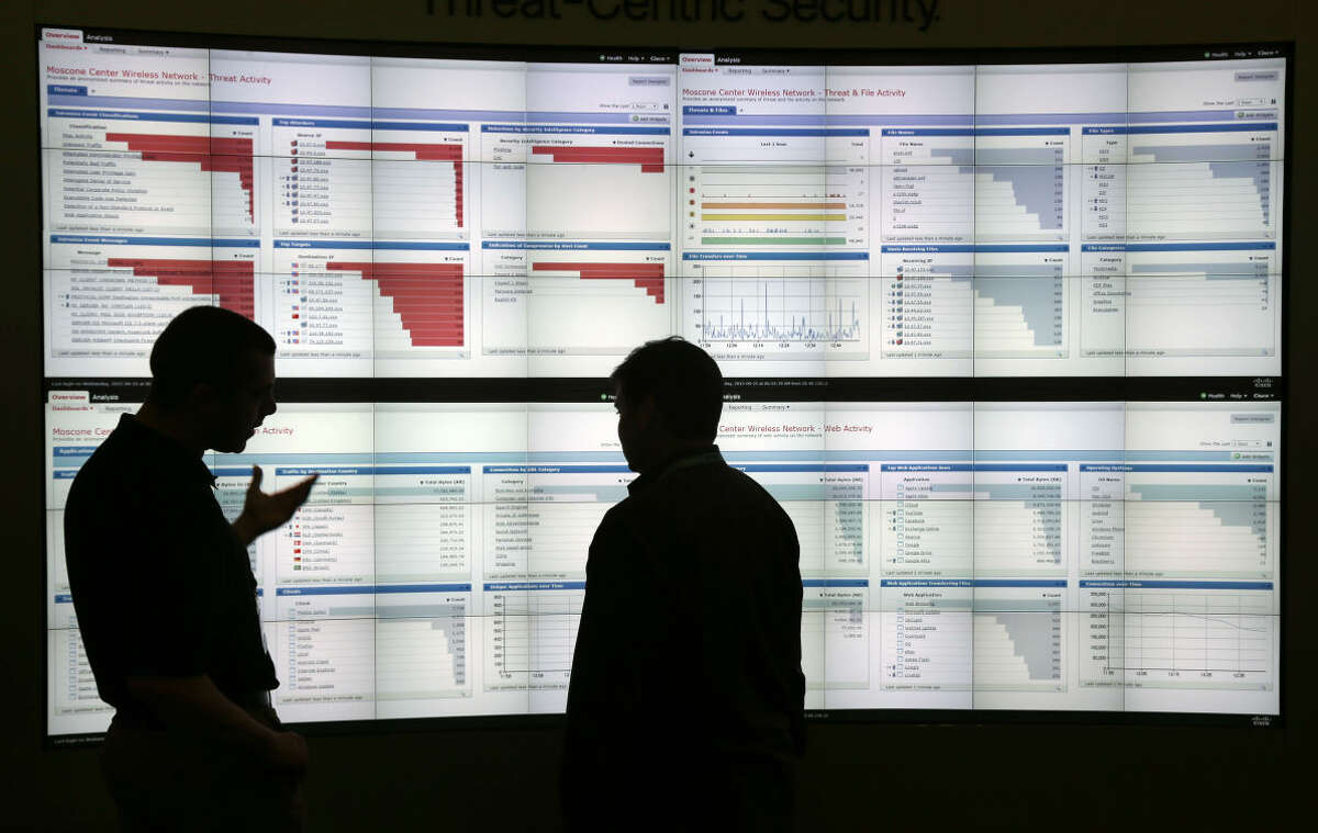 Stijn Vanveerdeghem, at left, an engineer with Cisco, shows graphics with live wireless traffic to FedEx employee Barry Poole during the RSA Conference on Wednesday, April 22, 2015, in San Francisco. Threat analysts, security vendors and corporate IT administrators have gathered here to talk about malicious software, spear-phishing and other attacks that can steal money or secrets from companies and consumers. (AP Photo/Marcio Jose Sanchez)