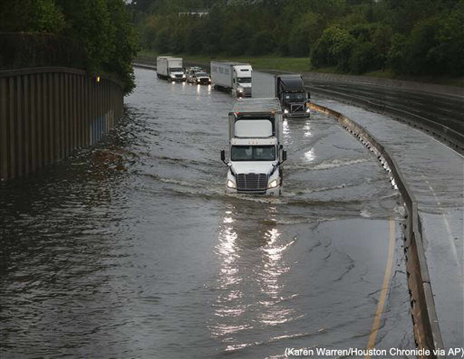 Trucks slowly drive through flood waters on North I-45 at North Main Street as White Oak Bayou comes over it's banks, flooding the freeway, Monday, April 18, 2016, in Houston. More than a foot of rain Monday in parts of Houston left scores of subdivisions and several major highways under water, knocked out power to thousands of people and closed schools. (Karen Warren/Houston Chronicle via AP) Photo: Karen Warren