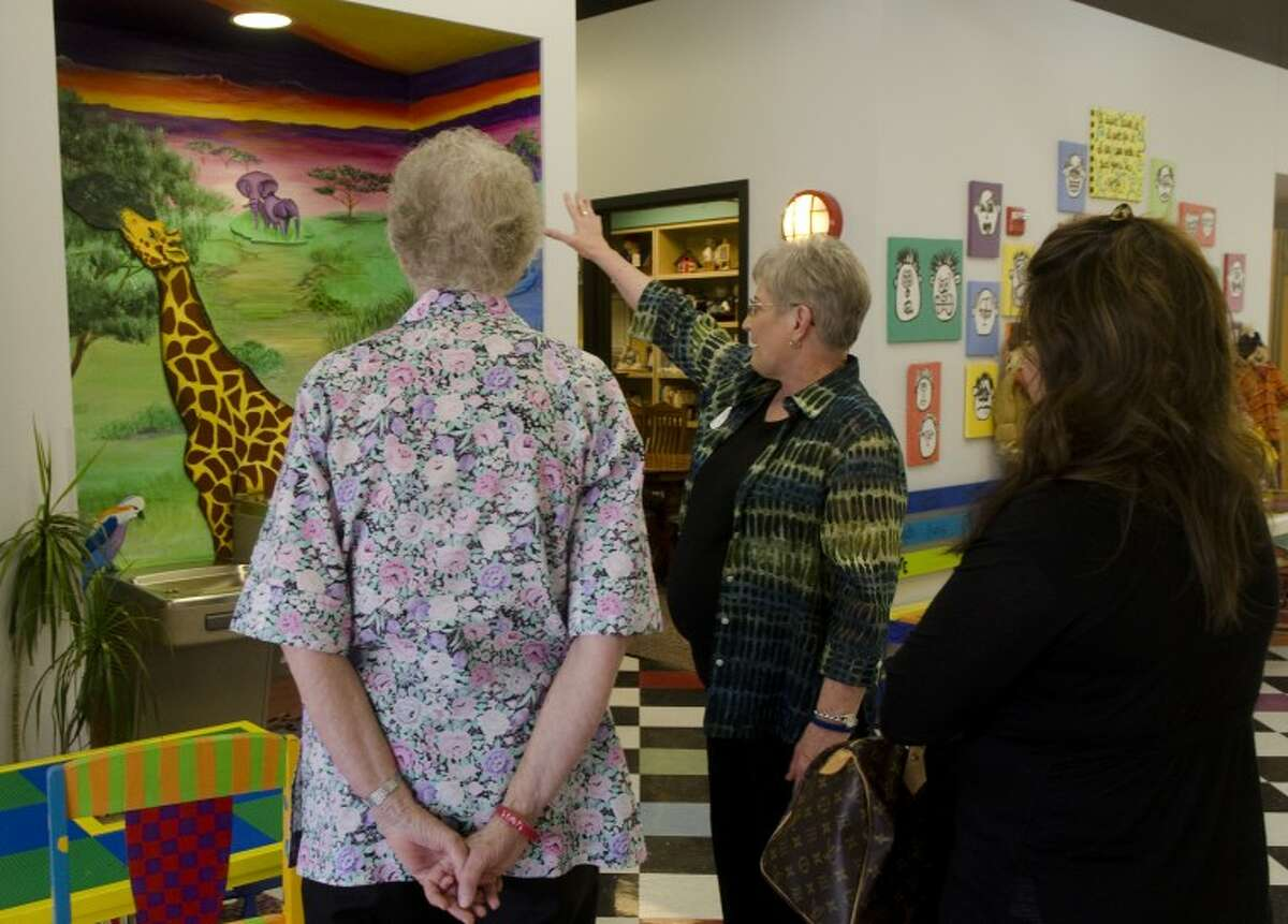 Suzanna Bechyn, center, with Rays of Hope, talks about how the artwork in the building was done by children attending the center, to Lois Petty and Andrea Nava Monday during an open house. Photo by Tim Fischer/Midland Reporter-Telegram