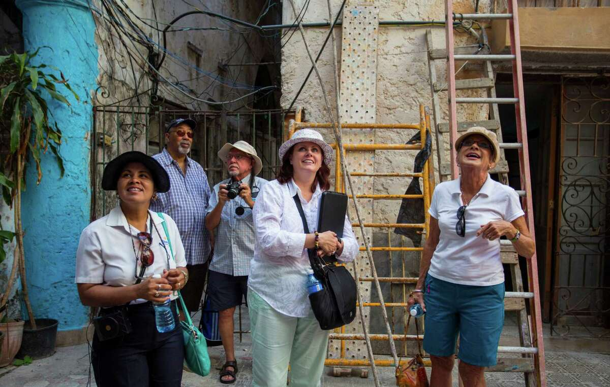 Pamela Boudrot, center, tour director for smarTours, and local guide Enedis Tamayo, left, lead a group of tourists in Havana.
