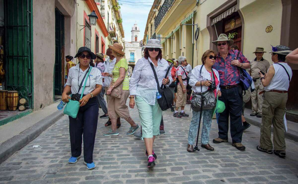 HOLD FOR SWAYNE HALL - SmarTours Tour Director Pamela Boudrot, center, and local tour guide Enedis Tamayo, left, lead their group of tourists in Havana, Cuba, Wednesday, April 20, 2016. (AP Photo/Desmond Boylan)