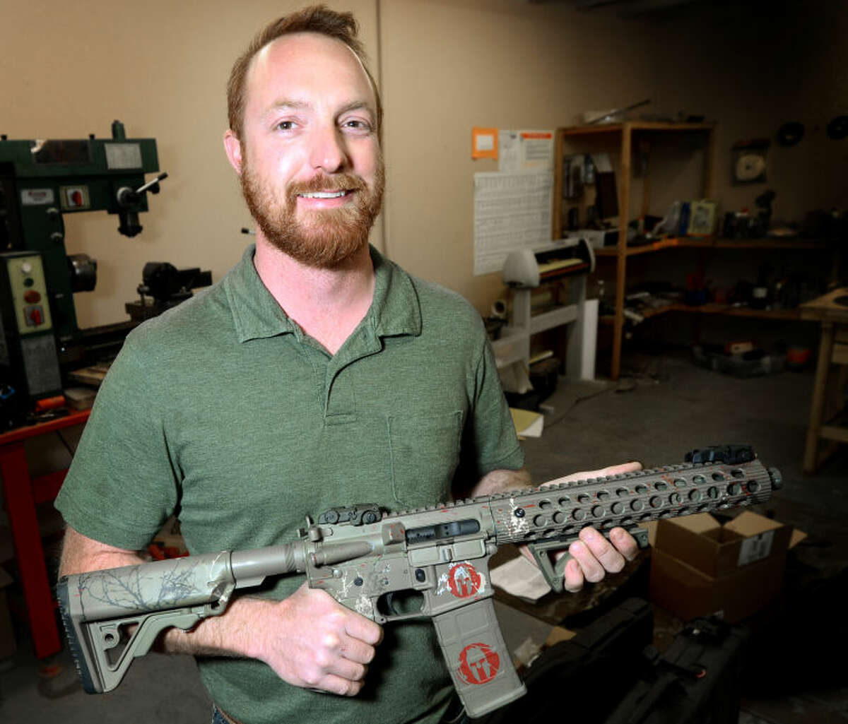Jamie Ehl, owner of Metal EFX, holds a .458 SOCOM short-barreled AR-15 rifle sporting a custom breakup green Cerakote finish in his shop Wednesday. Ehl adapts oilfield nickel-plating technology to create custom finishes for firearms. James Durbin/Reporter-Telegram