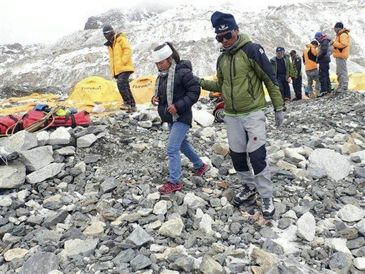 In this photo provided by Azim Afif, a man helps an injured woman after she is checked by a doctor at the International Mount Guide (IMG) camp at Everest Base Camp, Nepal on Sunday, April 26, 2015. An avalanche triggered by Nepal's massive earthquake slammed into a section of the Mount Everest mountaineering base camp Saturday, killing a number of people and left others unaccounted for. Afif and his team of four others from the Universiti Teknologi Malaysia (UTM) all survived the avalanche. (Azim Afif via AP)