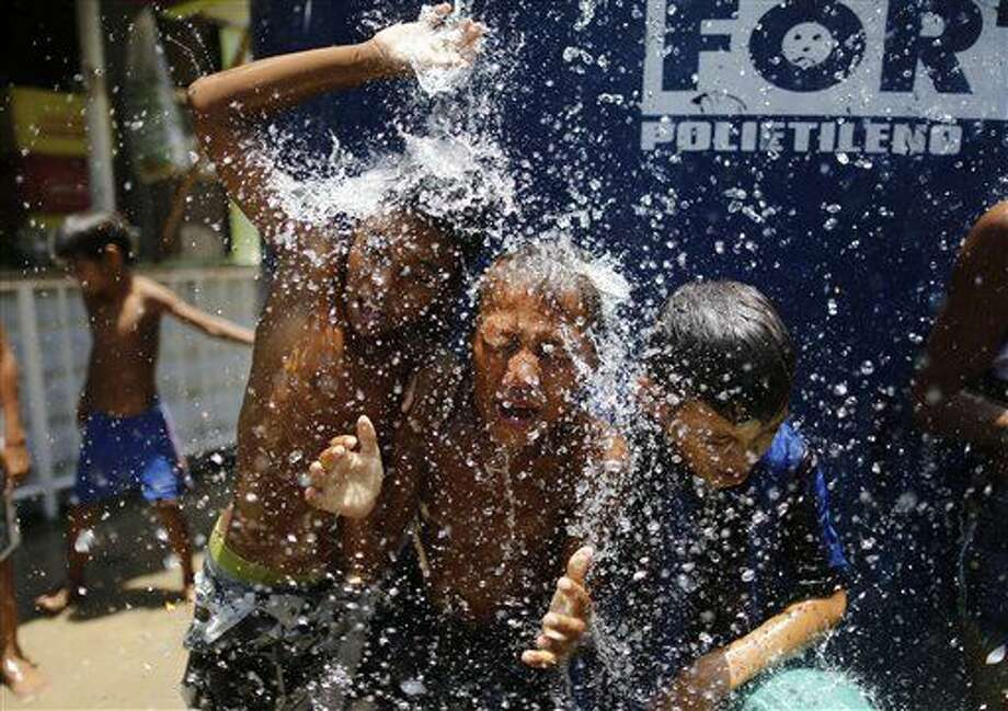 FILE - In this Jan. 29, 2015 file photo, children play under the water that they manage to spill over from a water tank, to cool off from the summer heat, at the Alemao Complex slum in Rio de Janeiro, Brazil. The next day it's unusually beastly hot, scientists say you can blame three-quarters of it on humans. As climate change gets worse around mid-century, that percentage of extremely hot days being caused by man-made greenhouse gases will push past 95 percent, according to a new study published Monday in the journal Nature Climate Change. (AP Photo/Leo Correa, File) Photo: Leo Correa