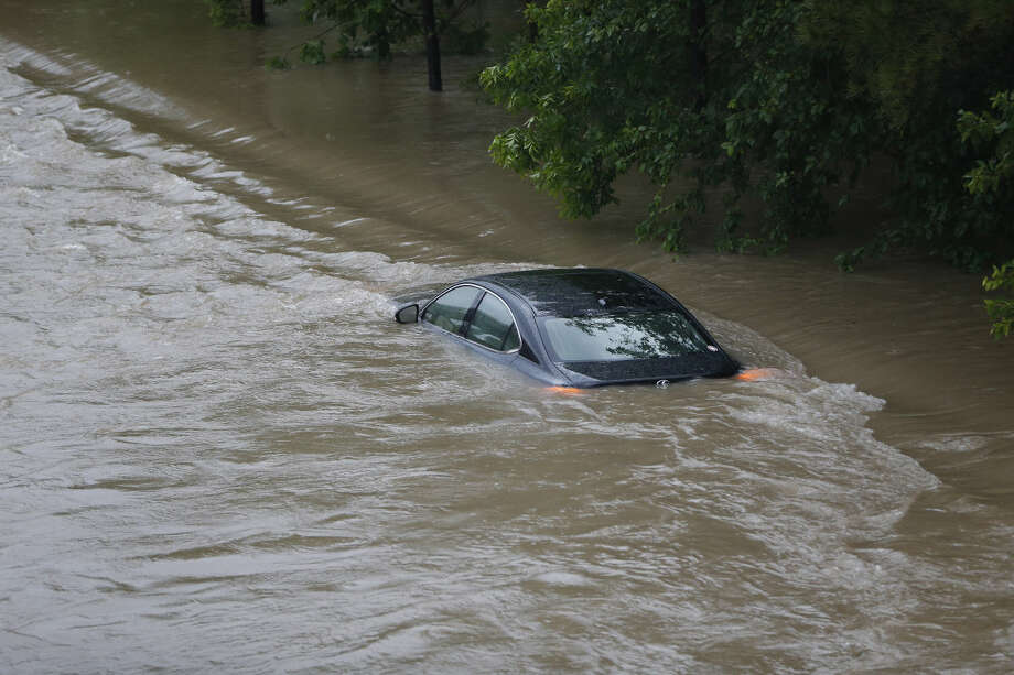 A car is stranded in flood water at I-10 under Houston Avenue as White Oak Bayou comes out of it's banks Monday, April 18, 2016, in Houston. ( Karen Warren / Houston Chronicle )