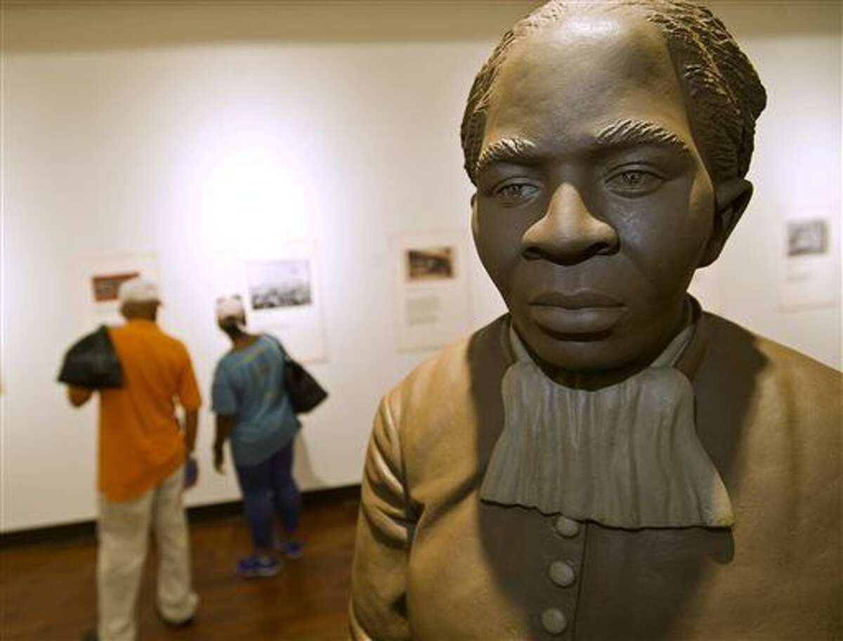 A statue of Harriett Tubman is the centerpiece of the History Gallery at the Tubman Museum, Wednesday, April 20, 2016, in Macon, Ga. Tubman, a prominent anti-slavery activist, will be the first African-American to appear on an American banknote and the first woman to appear on one in a century. Her portrait will replace former President Andrew Jackson, who will be moved to the back of the redesigned $20 bill. Ezzell and Beverly Hart Pittman from Columbia, SC, visit the museum Wednesday afternoon. (Woody Marshall/The Telegraph via AP