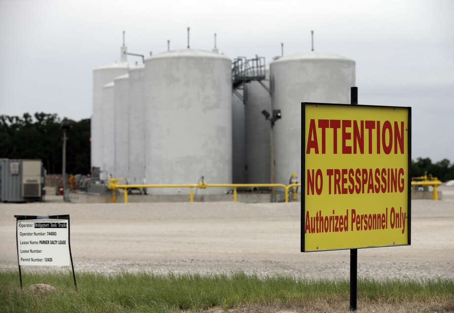 Signs warn against trespassing at a well injection site operated by Bridgeport Tank Trucks LTD., Saturday, June 21, 2014, in Azle, Texas. Earthquakes used to be unheard of on the vast stretches of prairie that unroll across Texas and Oklahoma. But in recent years, temblors have become commonplace. Oklahoma recorded 145 of them just between January and the start of May. (AP Photo/Tony Gutierrez) Photo: Tony Gutierrez