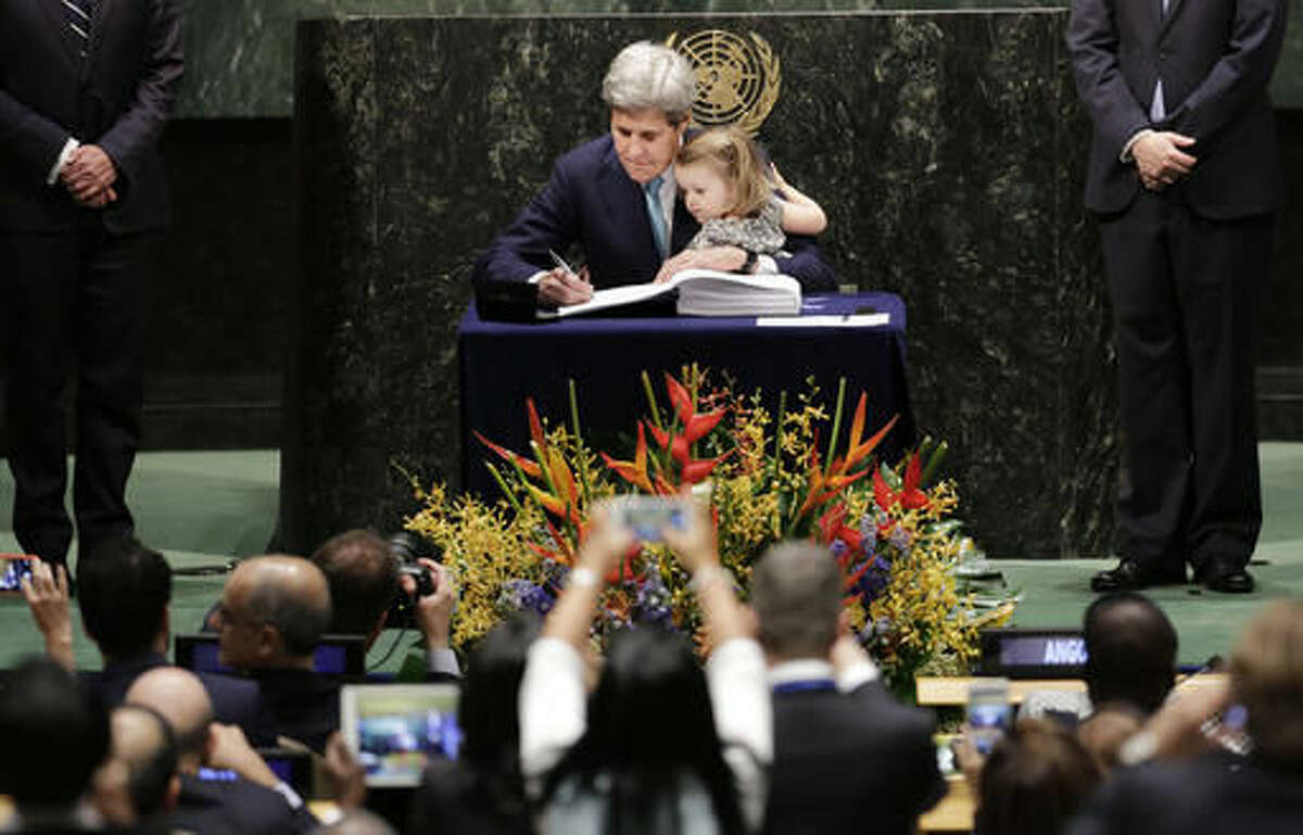 U.S. Secretary of State John Kerry holds his granddaughter Isabel Dobbs-Higginson as he signs the Paris Agreement on climate change, Friday, April 22, 2016 at U.N. headquarters. (AP Photo/Mark Lennihan)