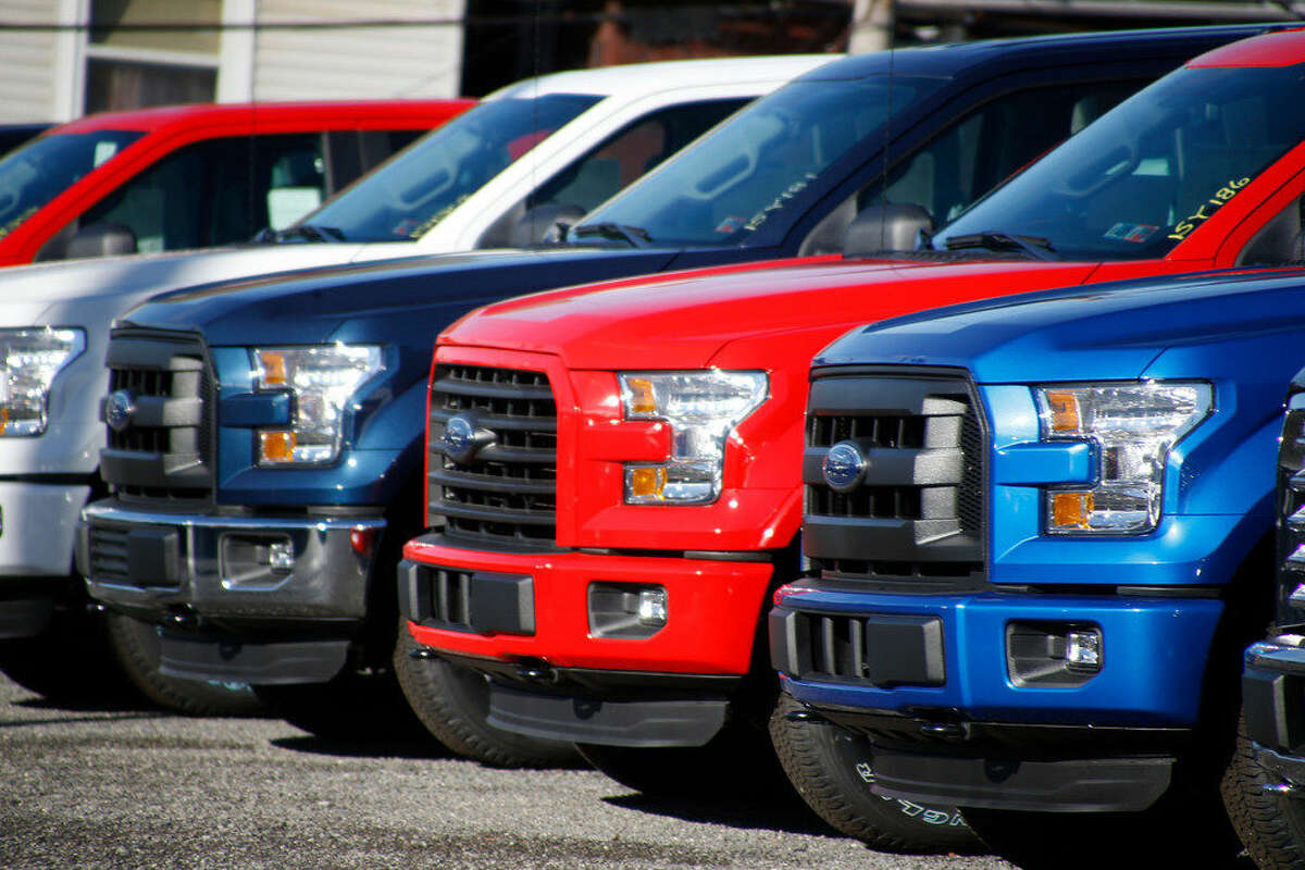 In this photo made on Thursday, Nov. 19, 2015, a row of 2015FordF-150pickup trucks are parked on the sales lot at Butler CountyFordin Butler, Pa. Two auto sales forecasting companies say Americans will buy more cars and trucks in December 2015 than any other month in more than a decade. LMC Automotive and J.D. Power are predicting that U.S. sales will hit 1.71 million this month, the highest number since sales reached 1.8 million in July of 2005. (AP Photo/Keith Srakocic)