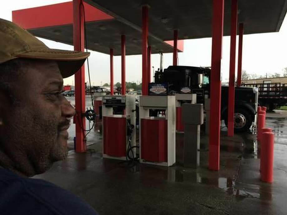 In this March 18, 2016 photo, Douglas Randall, a 60-year-old fisherman-turned-oilfield truck driver, stands on a rain-soaked day near his semi-truck parked at a gas station in Houma, LA., awaiting his next job. He is paid per load and works for oil companies, but he says work has dropped off by half due to the low price of oil and a reduction in drilling. Louisiana's oil industry is being clobbered by an unexpected worldwide oversupply of crude oil. The Louisiana Workforce Commission says the state has lost about 12,000 oil and gas jobs since 2014 as gas prices have ebbed. (AP Photo/Cain Burdeau) Photo: Gerald Herbert