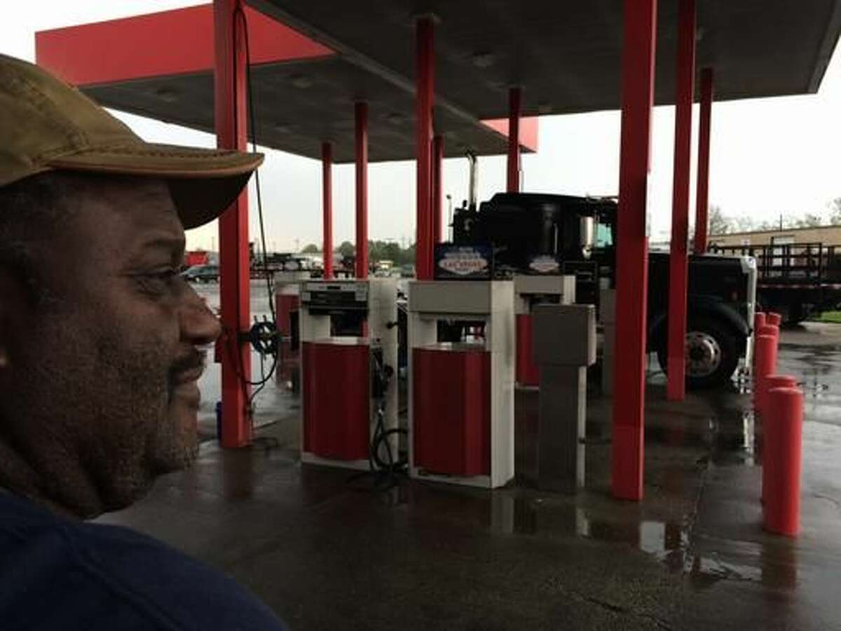 In this March 18, 2016 photo, Douglas Randall, a 60-year-old fisherman-turned-oilfield truck driver, stands on a rain-soaked day near his semi-truck parked at a gas station in Houma, LA., awaiting his next job. He is paid per load and works for oil companies, but he says work has dropped off by half due to the low price of oil and a reduction in drilling. Louisiana's oil industry is being clobbered by an unexpected worldwide oversupply of crude oil. The Louisiana Workforce Commission says the state has lost about 12,000 oil and gas jobs since 2014 as gas prices have ebbed. (AP Photo/Cain Burdeau)