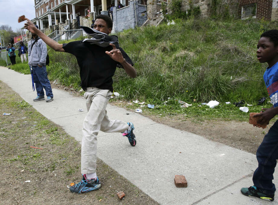 A boy throws a brick at police, Monday, April 27, 2015, during unrest following the funeral of Freddie Gray in Baltimore. Gray died from spinal injuries about a week after he was arrested and transported in a Baltimore Police Department van. (AP Photo/Patrick Semansky) Photo: Patrick Semansky