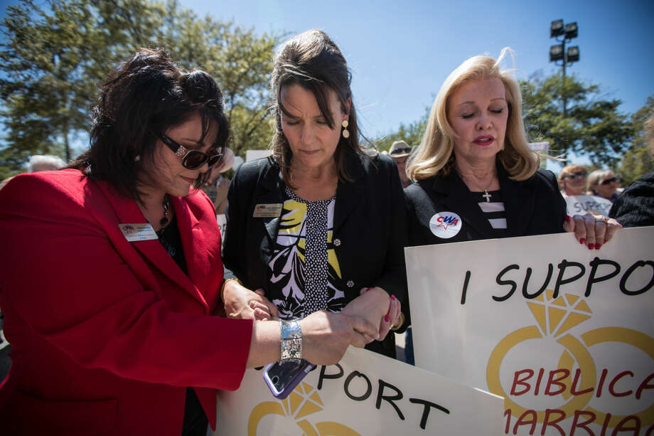 Members of the central Texas chapter of Concerned Women for America, a conservative Christian legislative action committee, pray while Alabama Supreme Court Chief Justice Roy Moore speaks at the Defense of the Texas Marriage Amendment Rally outside of the Texas State Capitol on Monday, March 23, 2015 in Austin, Texas. (AP Photo/ Tamir Kalifa) Photo: Tamir Kalifa