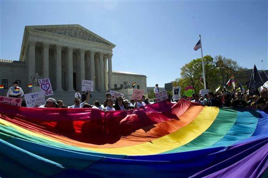 Demonstrators stand in front of a rainbow flag of the Supreme Court in Washington, Tuesday, April 28, 2015. The Supreme Court is set to hear historic arguments in cases that could make same-sex marriage the law of the land. The justices are meeting Tuesday to offer the first public indication of where they stand in the dispute over whether states can continue defining marriage as the union of a man and a woman, or whether the Constitution gives gay and lesbian couples the right to marry. (AP Photo/Jose Luis Magana) Photo: Jose Luis Magana