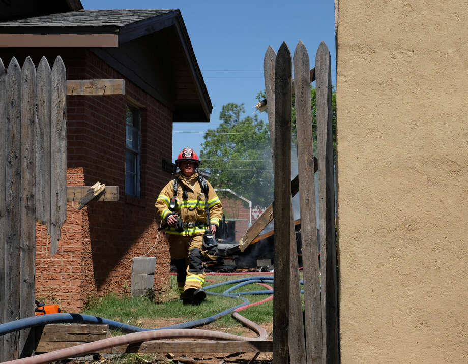 A fireman walks from the smoking remnants of a shed behind a home that caught fire in southeast Midland Friday afternoon.  Photo: Erin Stone
