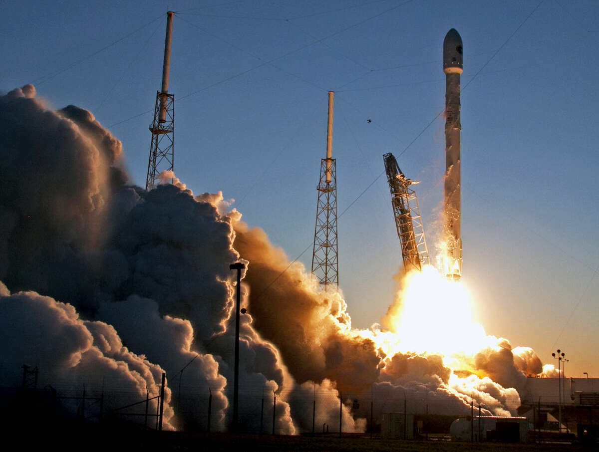 FILE - In this Feb. 11, 2015 file photo, a Falcon 9 SpaceX rocket lifts off from launch complex 40 at the Cape Canaveral Air Force Station in Cape Canaveral, Fla. In Texas, two internet billionaires whose strategies and personalities seem worlds apart are playing host to a 21st-century space race. Low-key Amazon founder Jeff Bezos' Blue Origin is in West Texas. Elon Musk, who helped start PayPal, heads high-profile SpaceX company 600 miles to the southeast. (AP Photo/John Raoux, File)