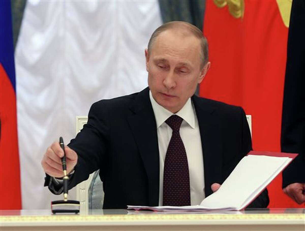 In this March 21, 2014, photo, Russian President Vladimir Putin signs bills making Crimea part of Russia in the Kremlin in Moscow. U.S. sanctions against a Russian bank and the Kremlin's inner circle have pinched Moscow, but if the goal is to get Putin to roll his forces out of Crimea or prevent him from doing any more land grabs, their effectiveness remains in doubt. Putin has mocked the punitive steps President Barack Obama has taken so far in their post-Cold War game of chess _ or chicken. (AP Photo/Sergei Chirikov, Pool)