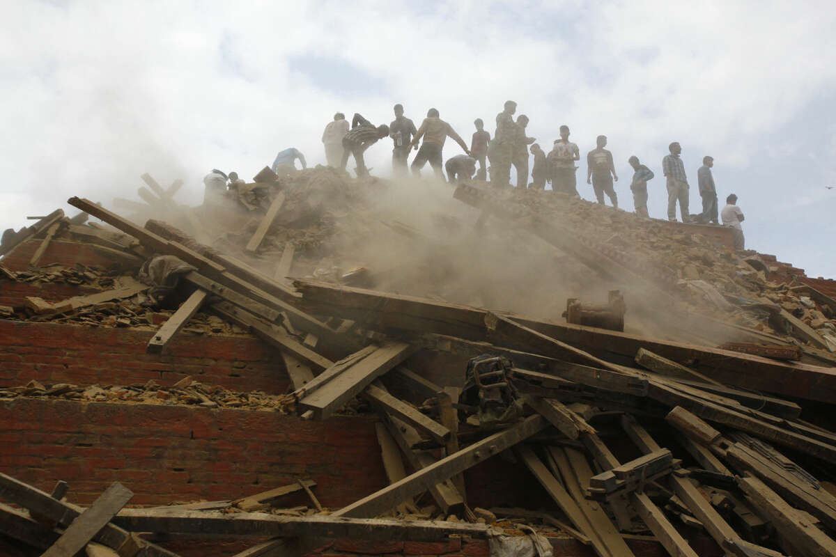 In this April 25, 2015 photo, volunteers help remove debris of a building that collapsed at Durbar Square, after an earthquake in Kathmandu, Nepal. A strong magnitude-7.8 earthquake shook Nepal's capital and the densely populated Kathmandu Valley before noon Saturday, causing extensive damage with toppled walls and collapsed buildings, officials said. (AP Photo/Niranjan Shrestha, File)