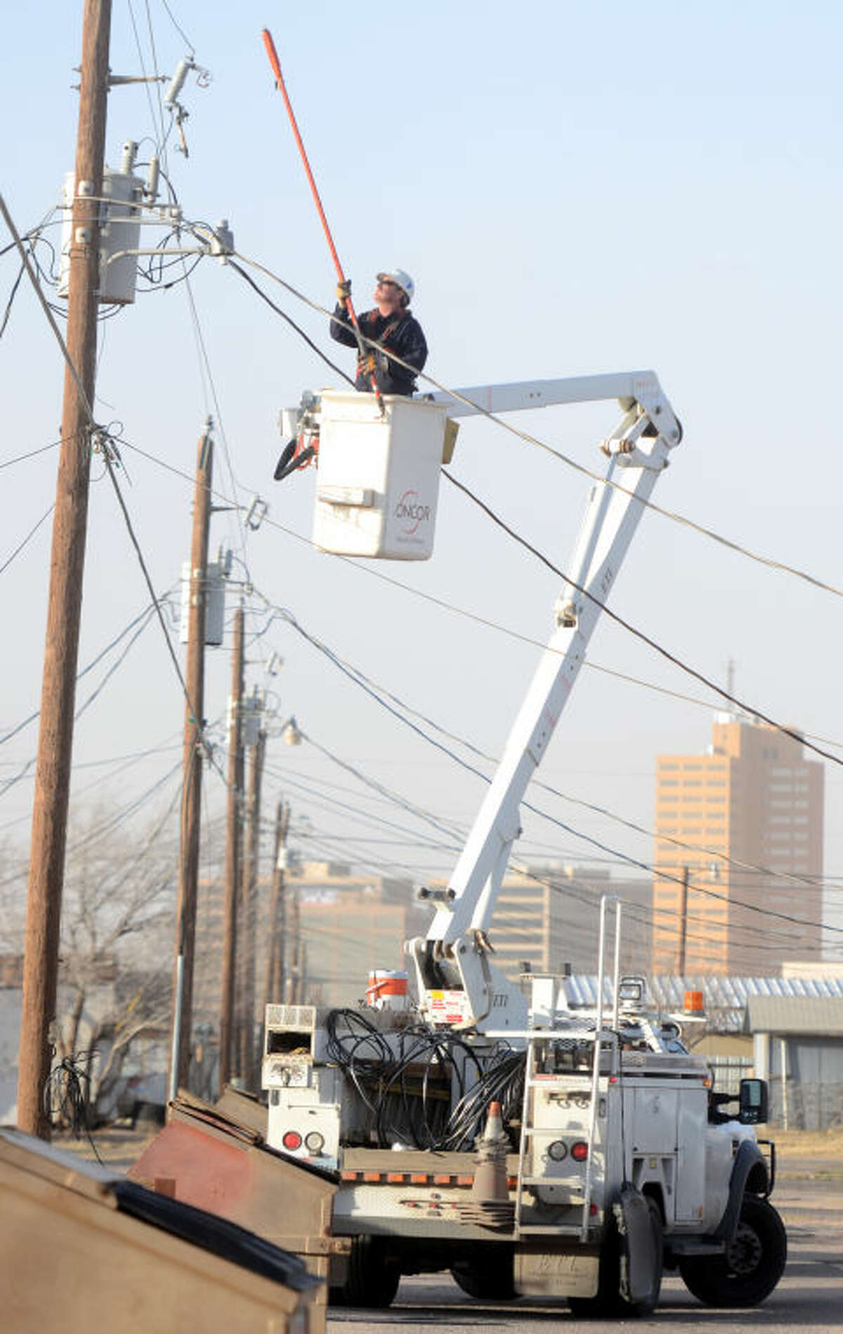 An Oncor Energy worker makes repairs to a power line in an alley near the intersection of Hicks Ave. and Belmont St. during a windstorm Tuesday. James Durbin/Reporter-Telegram