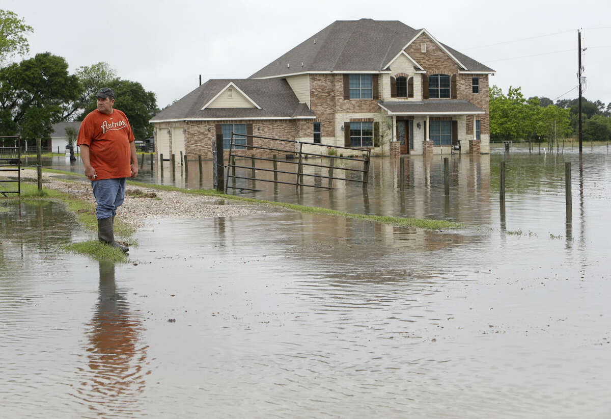 """Donald Treichel looks at the flood water along Cypress Rosehill Rd. in Cypress where the water is up to his doorstep shown Monday, April 18, 2016. He said, """"I've lived here 48 years and never seen it this high before."""" ( Melissa Phillip / Houston Chronicle )"""
