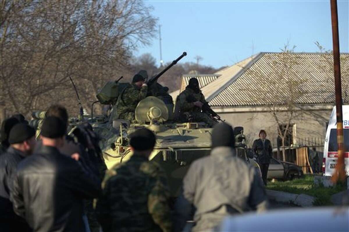 Soldiers in unmarked uniforms sit atop APC at the gate of the Belbek base near the port city of Sevastopol, Crimea, Saturday, March 22, 2014. Pro-Russian forces stormed the Ukrainian Belbek air force base in Crimea, firing shots and smashing through concrete walls with armored personnel carriers, according to an Associated Press journalist. At least one person was wounded, the base commander said. (AP Photo/Ivan Sekretarev)