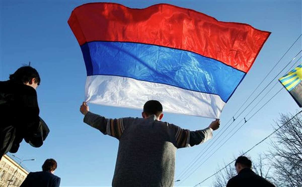 An activists carries a Russian flag during a rally at a central square in Donetsk, eastern Ukraine, Sunday, March 23, 2014. About 5,000 people demonstrated in Donetsk in favor of holding a referendum on secession and absorption into Russia similar to Crimea's. (AP Photo/Sergei Grits)