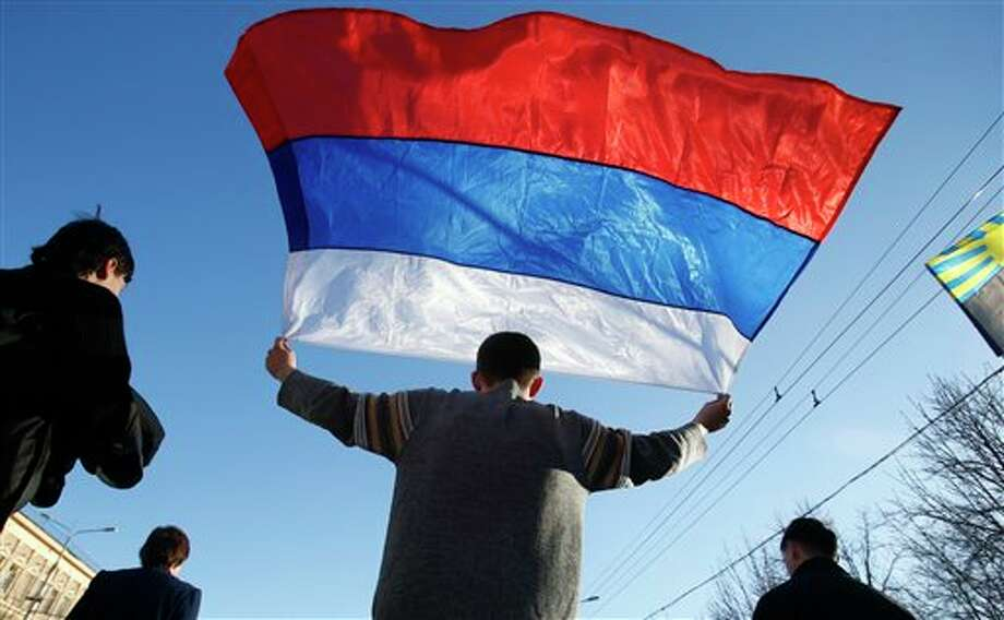 An activists carries a Russian flag during a rally at a central square in Donetsk, eastern Ukraine, Sunday, March 23, 2014. About 5,000 people demonstrated in Donetsk in favor of holding a referendum on secession and absorption into Russia similar to Crimea's. (AP Photo/Sergei Grits) Photo: Sergei Grits / AP
