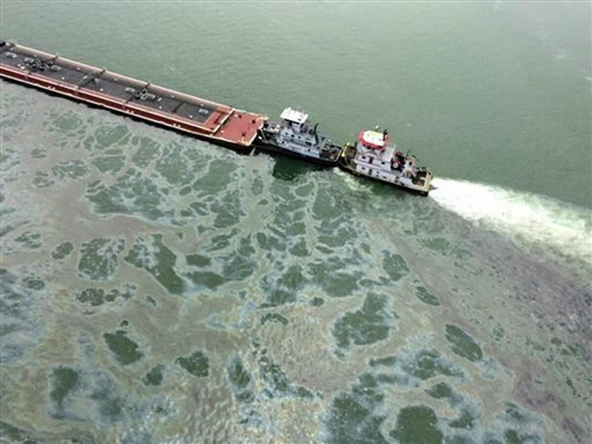 A barge loaded with marine fuel oil sits partially submerged in the Houston Ship Channel, March 22, 2014. The bulk carrier Summer Wind, reported a collision between the Summer Wind and the barge, containing 924,000 gallons of fuel oil. The barge collided with a ship in Galveston Bay on Saturday, leaking an unknown amount of the fuel into the popular bird habitat as the peak of the migratory shorebird season was approaching. (AP Photo/U.S. Coast Guard, PO3 Manda Emery)