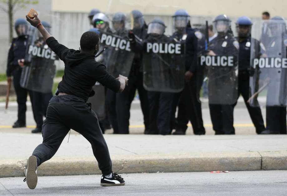 A man throws a brick at police Monday, April 27, 2015, following the funeral of Freddie Gray in Baltimore. Gray died from spinal injuries about a week after he was arrested and transported in a Baltimore Police Department van. (AP Photo/Patrick Semansky) Photo: Patrick Semansky
