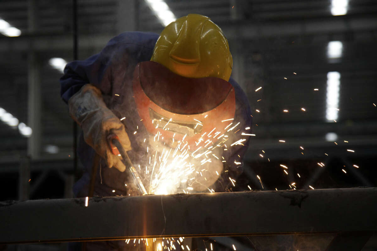 In this March 20, 2015 photo, a worker welds a building beam at the Broad Sustainable Building Co. in Yueyang in central China's Hunan Province. The Chinese construction company is claiming to be the world's fastest builder after erecting a 57-story skyscraper in 19 working days in central China. The company put up the rectangular, glass-and-steel Mini Sky City using a modular method, assembling three floors per day, company vice president Xiao Changgeng said. (AP Photo/Peng Peng)