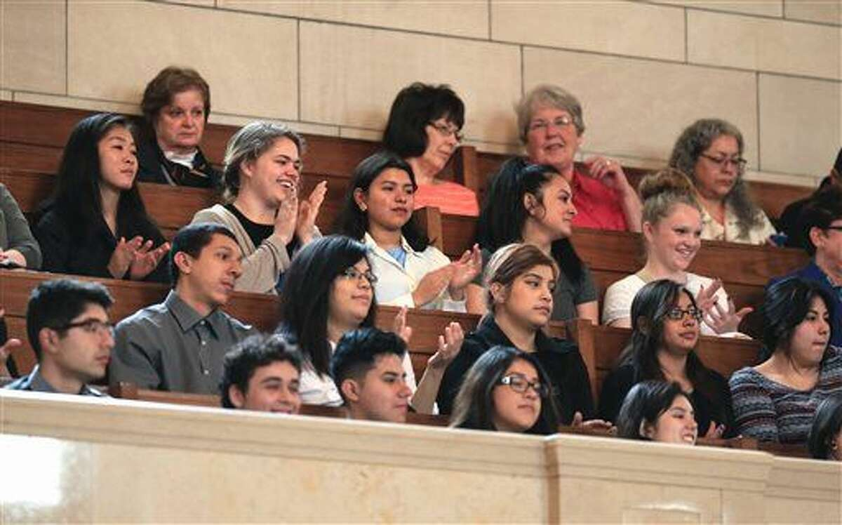Spectators who were brought to the U.S. illegally as children, applaud in the balcony overlooking the Legislative Chamber at the State Capitol in Lincoln, Neb., Wednesday, April 20, 2016, as Nebraska lawmakers overrode Gov. Pete Ricketts veto of a bill that would allow certain immigrants to get professional licenses. The bill would apply to young immigrants who entered the country illegally but received temporary legal status under a 2012 Obama administration policy. (AP Photo/Nati Harnik)