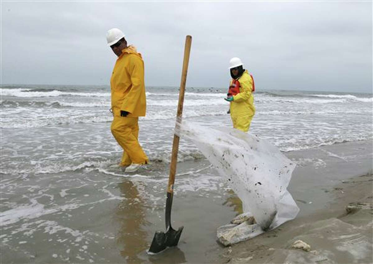 Workers walk along East Beach in Galveston, Texas, looking for pieces of oil tar, Monday, March 24, 2014. Thousands of gallons of tar-like oil spilled into the major U.S. shipping channel after a barge ran into a ship Saturday. (AP Photo/Pat Sullivan)