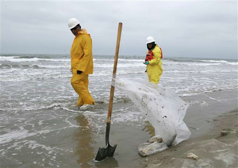 Workers walk along East Beach in Galveston, Texas, looking for pieces of oil tar, Monday, March 24, 2014. Thousands of gallons of tar-like oil spilled into the major U.S. shipping channel after a barge ran into a ship Saturday. (AP Photo/Pat Sullivan) Photo: Pat Sullivan / AP