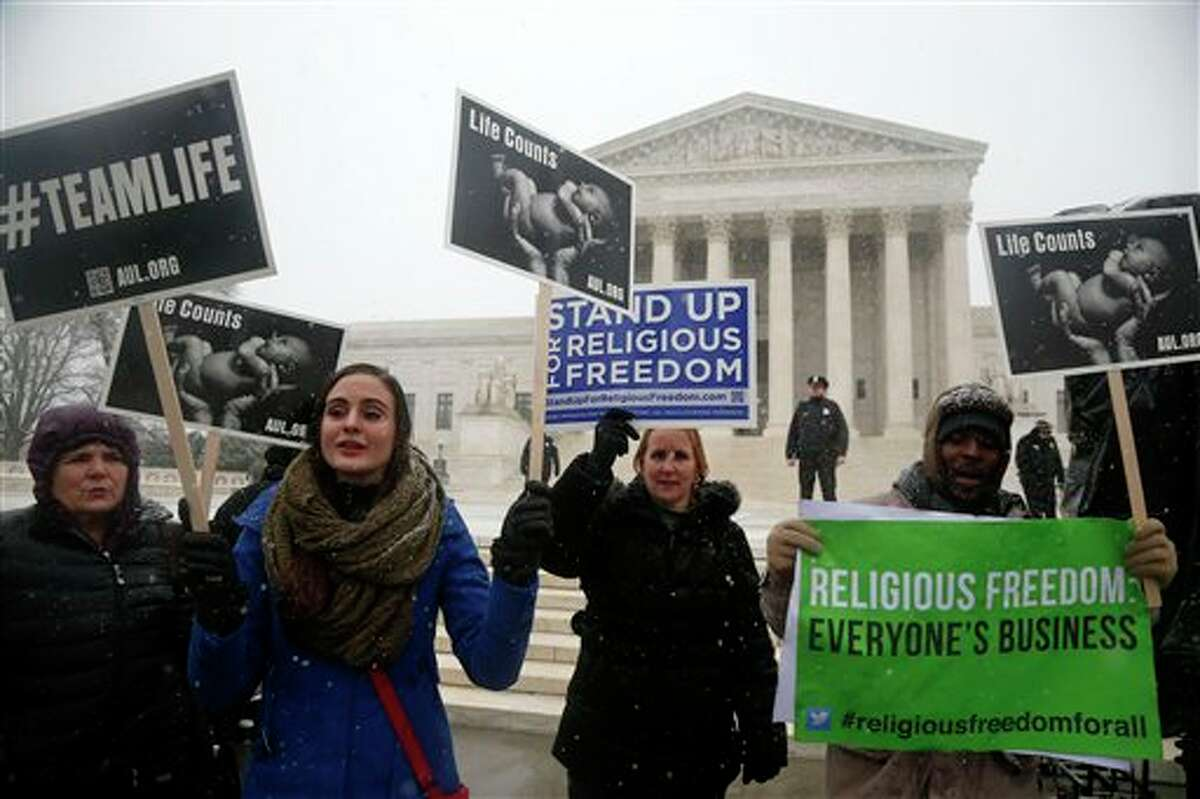 Demonstrators participate in a rally in front of the Supreme Court in Washington, Tuesday, March 25, 2014, as the court heard oral arguments in the challenges of President Barack Obama's health care law requirement that businesses provide their female employees with health insurance that includes access to contraceptives. Supreme Court justices are weighing whether corporations have religious rights that exempt them from part of the new health care law that requires coverage of birth control for employees at no extra charge. (AP Photo/Charles Dharapak)