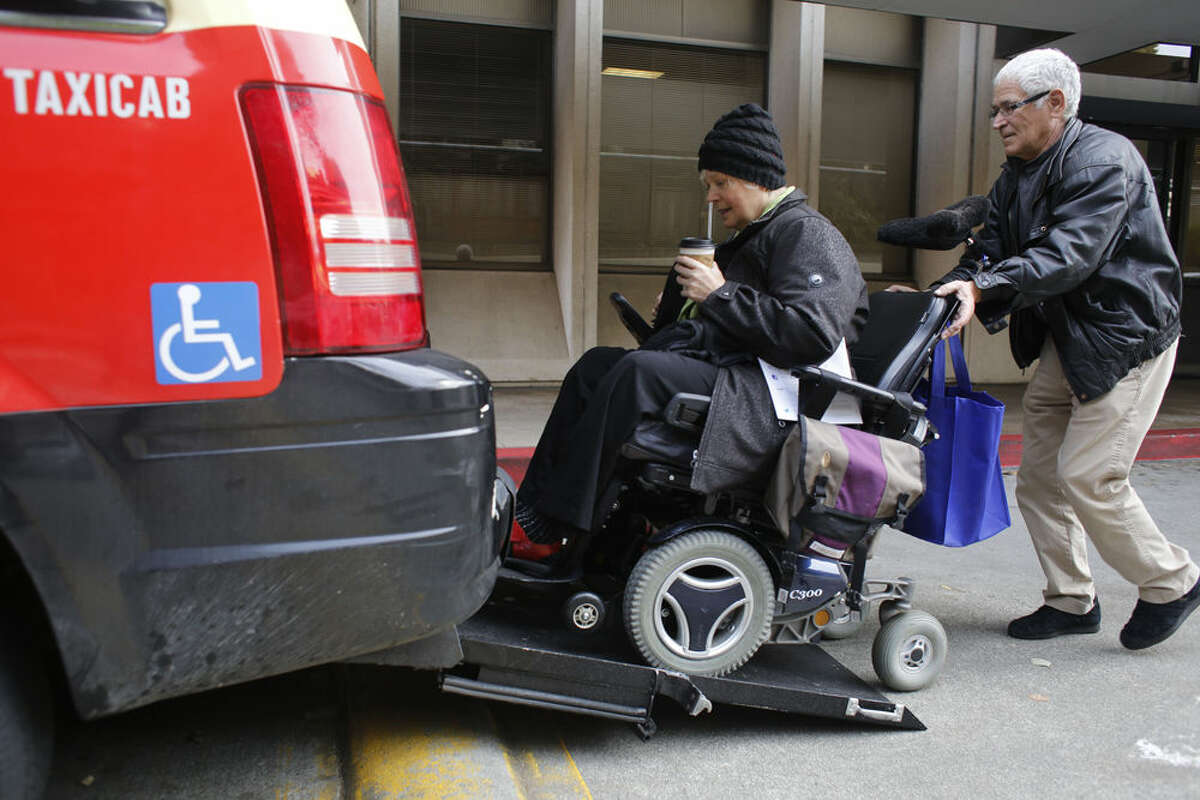 With the help of a cab driver who wished to remain anonymous, Peggy Costa boards an Arrow Cab equipped to accommodate people with disabilities on Wednesday Feb. 12, 2014.