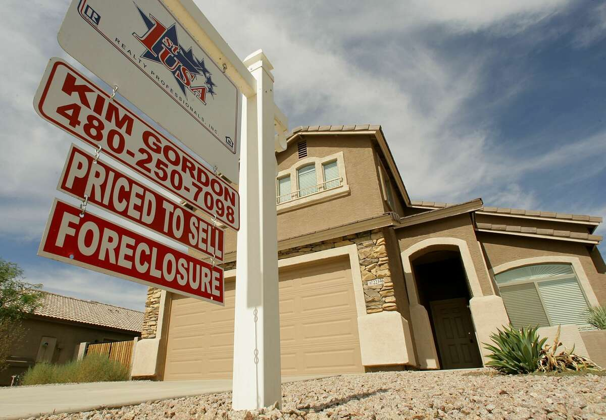 FILE - In this Sept. 26, 2007 file photo, a realty sign stands in front of one of the many homes that are in foreclosure in the Villages of Queen Creek in Queen Creek, Ariz. The number of U.S. homes repossessed by lenders fell to the lowest level in nearly six years last month amid a resurgent housing market and rising home prices, the latest evidence that the nation's foreclosure woes are easing, according to new data from foreclosure listing firm RealtyTrac Inc. (AP Photo/Ross D. Franklin, file)