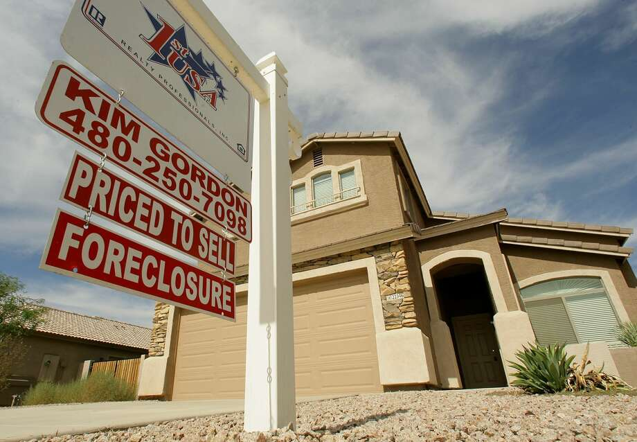 FILE - In this Sept. 26, 2007 file photo, a realty sign stands in front of one of the many homes that are in foreclosure in the Villages of Queen Creek in Queen Creek, Ariz. The number of U.S. homes repossessed by lenders fell to the lowest level in nearly six years last month amid a resurgent housing market and rising home prices, the latest evidence that the nation's foreclosure woes are easing, according to new data from foreclosure listing firm RealtyTrac Inc. (AP Photo/Ross D. Franklin, file) Photo: Ross D. Franklin