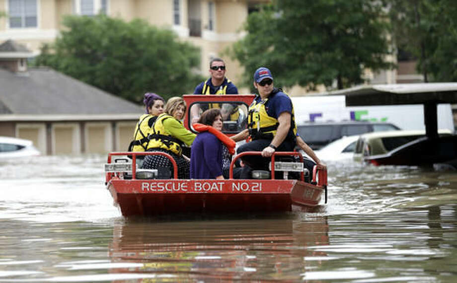 Residents are evacuated from their flooded apartment complex Tuesday, April 19, 2016, in Houston. Storms have dumped more than a foot of rain in the Houston area, flooding dozens of neighborhoods. (AP Photo/David J. Phillip) Photo: David J. Phillip