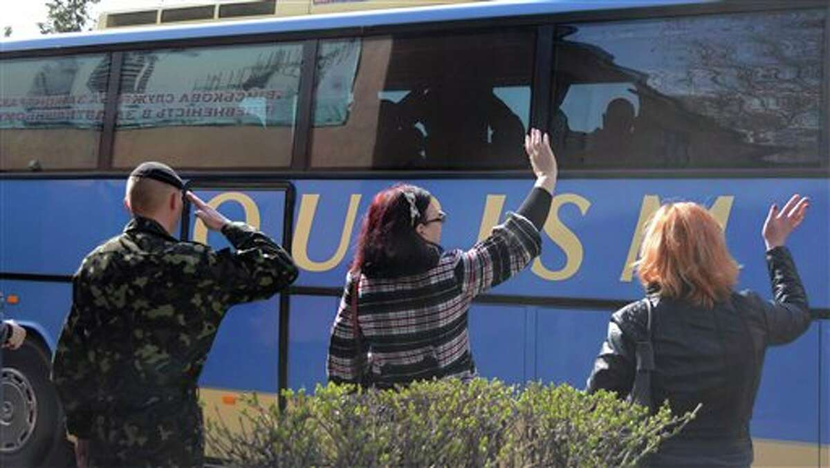 Women wave and a Ukrainian marine salutes Ukrainian marines in Feodosia, Crimea, Tuesday, March 25, 2014. In Crimea, Ukrainian soldiers piled onto buses and began their journey to Ukrainian territory on Tuesday, as former comrades saluted them from outside a base overrun by Russian forces. (AP Photo/Valeriy Kulyk)