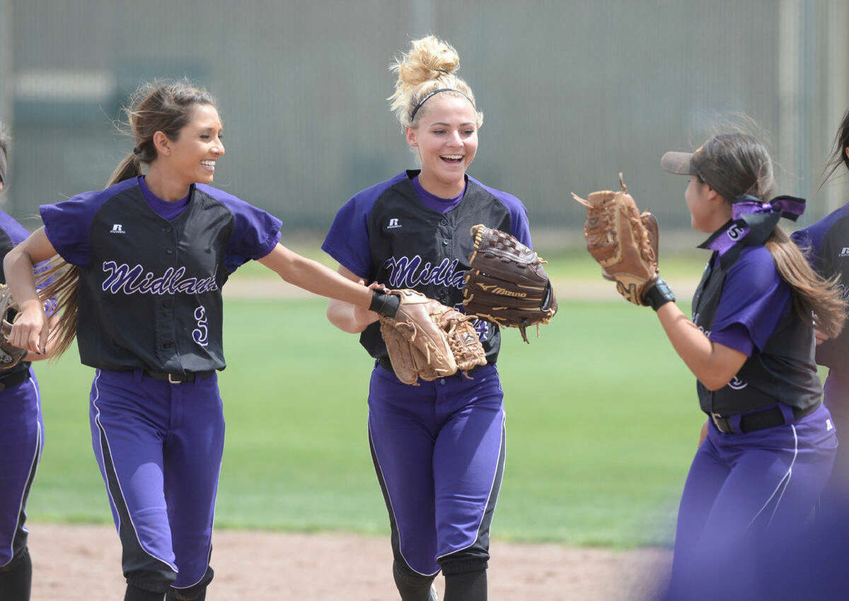 Midland High's Ashley McClellan (center) is congratulated by teammates after making a diving catch to finish out the inning against Lee on Saturday, April 23, 2016, at Gene Smith Field. James Durbin/Reporter-Telegram