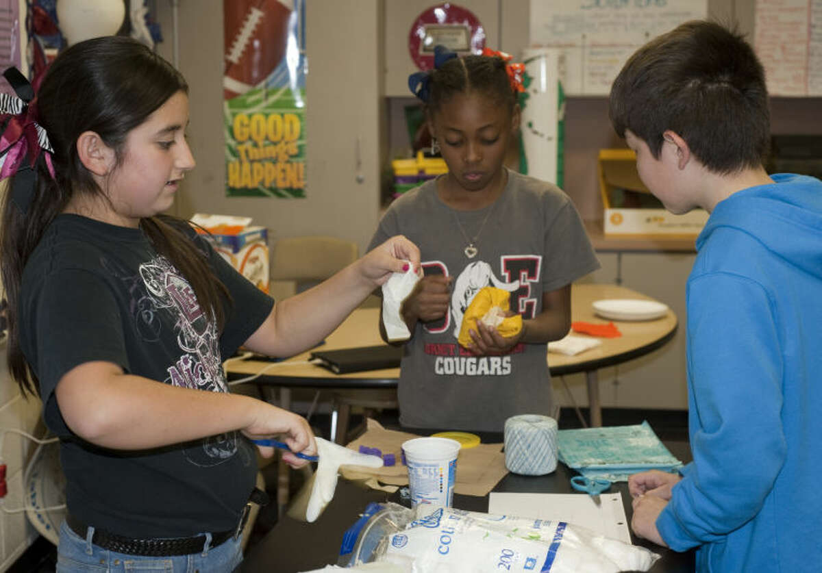 Jessica Pinal, Zaria Green and Xavier Mancias work on wrapping and padding their egg to be dropped on the playground Friday during Science Club at Burnet Elementary. Tim Fischer\Reporter-Telegram
