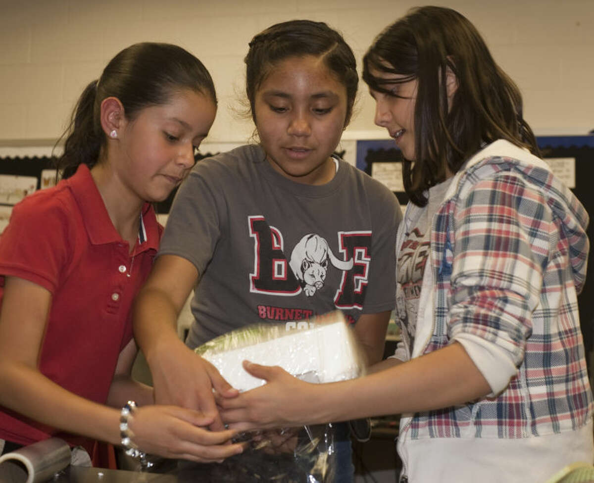 Lindsey Ovalle, Adriana Barraza and Camila Ronquillo work on wrapping and padding their egg to be dropped on the playground Friday during Science Club at Burnet Elementary. Tim Fischer\Reporter-Telegram
