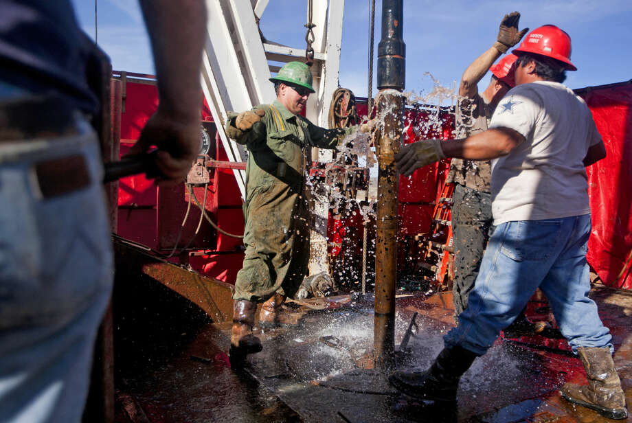 Guy Cummings (left), Carl Merworth (center, rear) and Desiderio Castillo (right) attach a 90-foot section of pipe onto the end of an active drill pipe on the drilling floor of Robinson Drilling rig #4 on Wednesday, Feb. 17, 2016, in Midland County. James Durbin/Reporter-Telegram