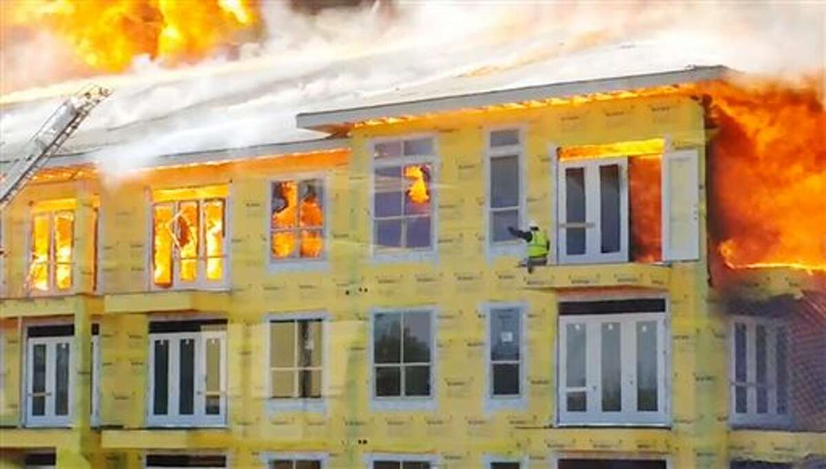 In this image taken from video provided by Karen Jones, a worker waves to rescue workers for help from the fifth floor balcony before swinging down to the one below as firefighters battle a five-alarm fire at a construction site Tuesday, March 25, 2014, in Houston. The cellphone video, shot by Karen Jones from her nearby office, shows the dramatic rescue of the worker from the burning apartment complex that was under construction. (AP Photo/Karen Jones) NO SALES