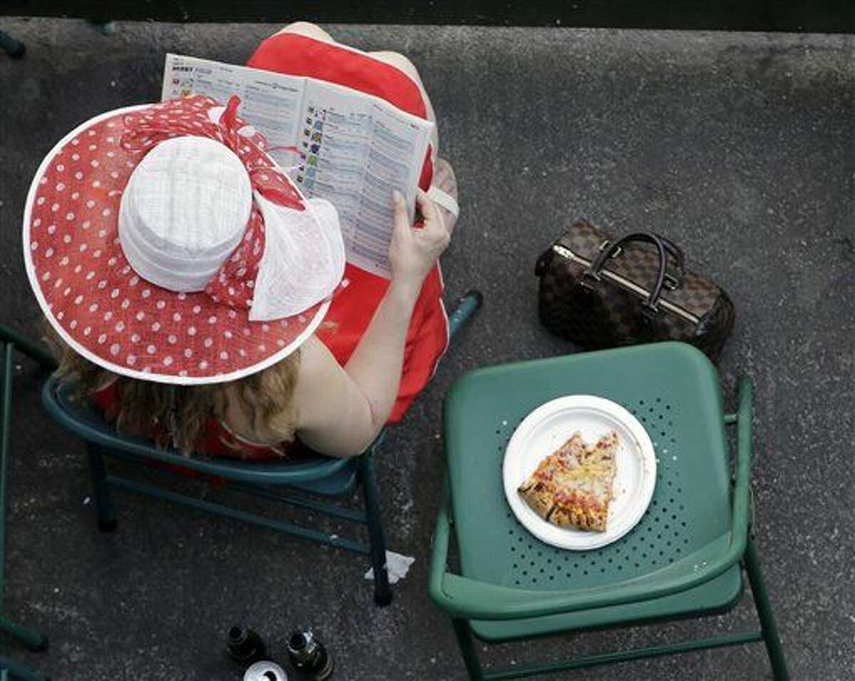 A fan reads a program before the 141st running of the Kentucky Derby horse race at Churchill Downs Saturday, May 2, 2015, in Louisville, Ky. (AP Photo/Charlie Riedel)