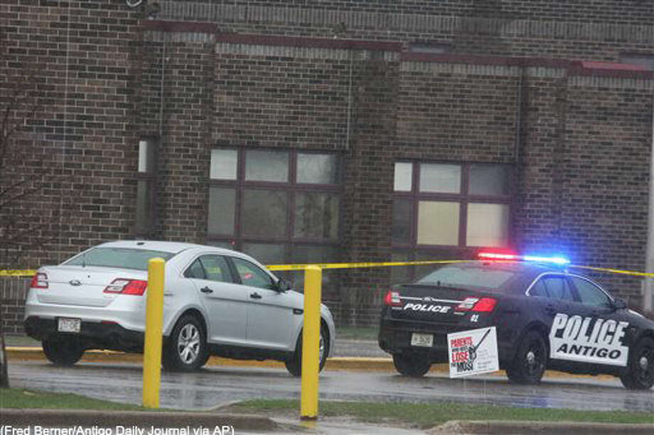 Two Antigo police department vehicles sit in front of the entrance to Antigo High School, Sunday, April 24, 2016, where an 18-year-old gunman opened fire late Saturday outside of a prom at the school. The shooter wounded two students before a police officer who was in the parking lot fatally shot him, authorities said Sunday. (Fred Berner/Antigo Daily Journal via AP) MANDATORY CREDIT Photo: Fred Berner